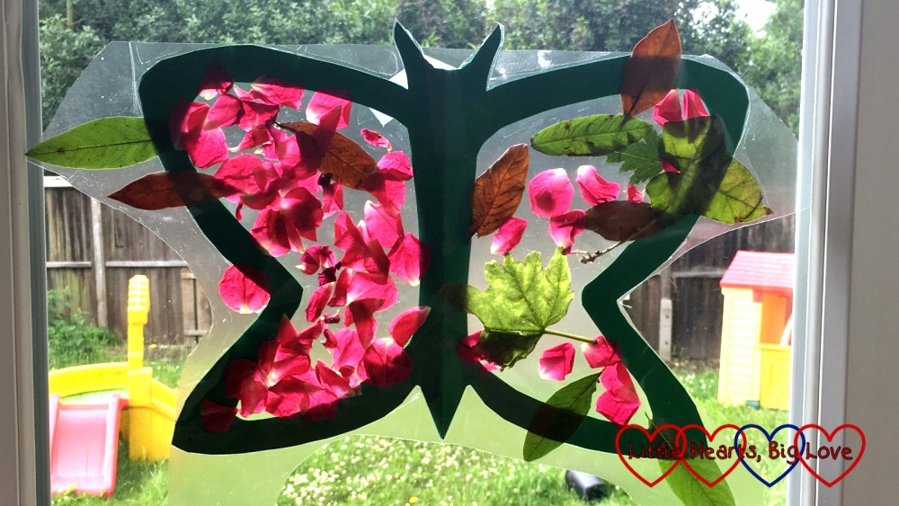 The finished butterfly with leaves and petals stuck to the wings and a border of sticky back plastic around the butterfly shape which is used to stick it to the window