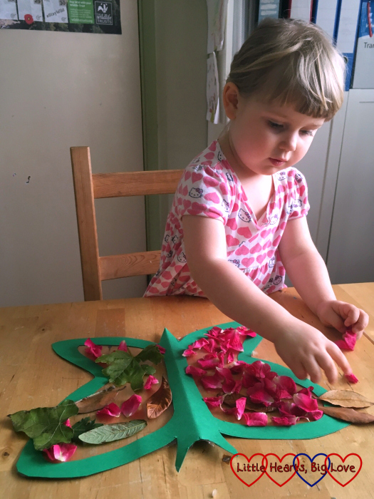 Sophie decorating the butterfly with leaves and petals