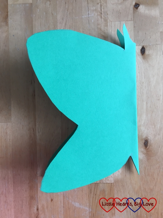 A butterfly shape cut out of green cardboard
