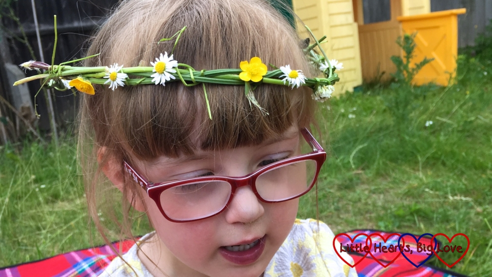 Jessica wearing a flower crown made from woven grass, daisies, buttercups and white clover