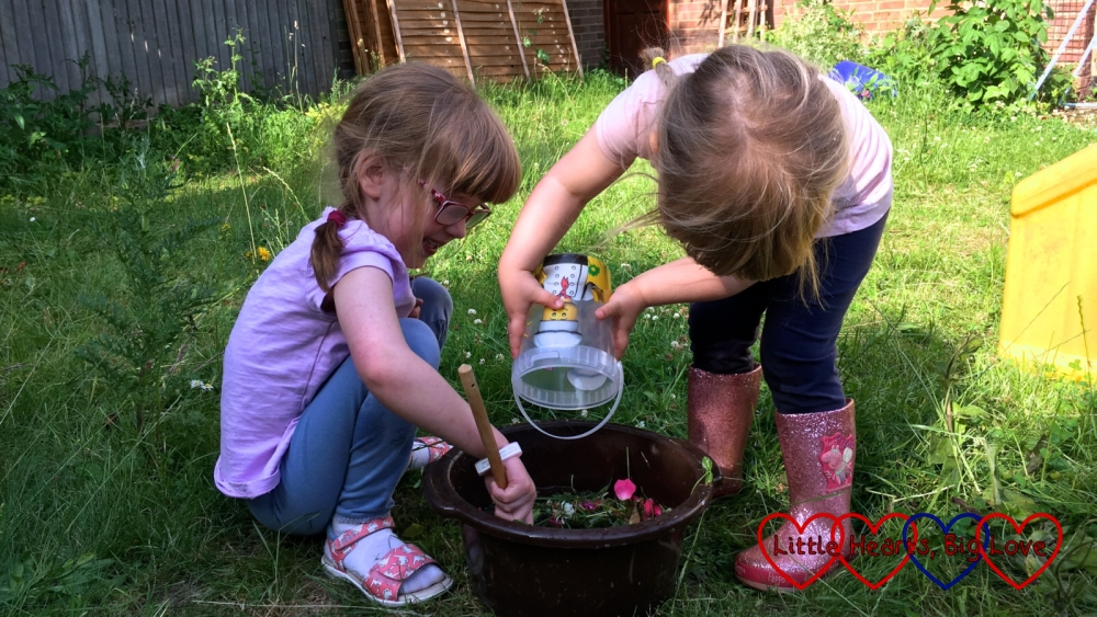 Sophie emptying the 'ingredients' into the bowl while Jessica stirs the fairy potion