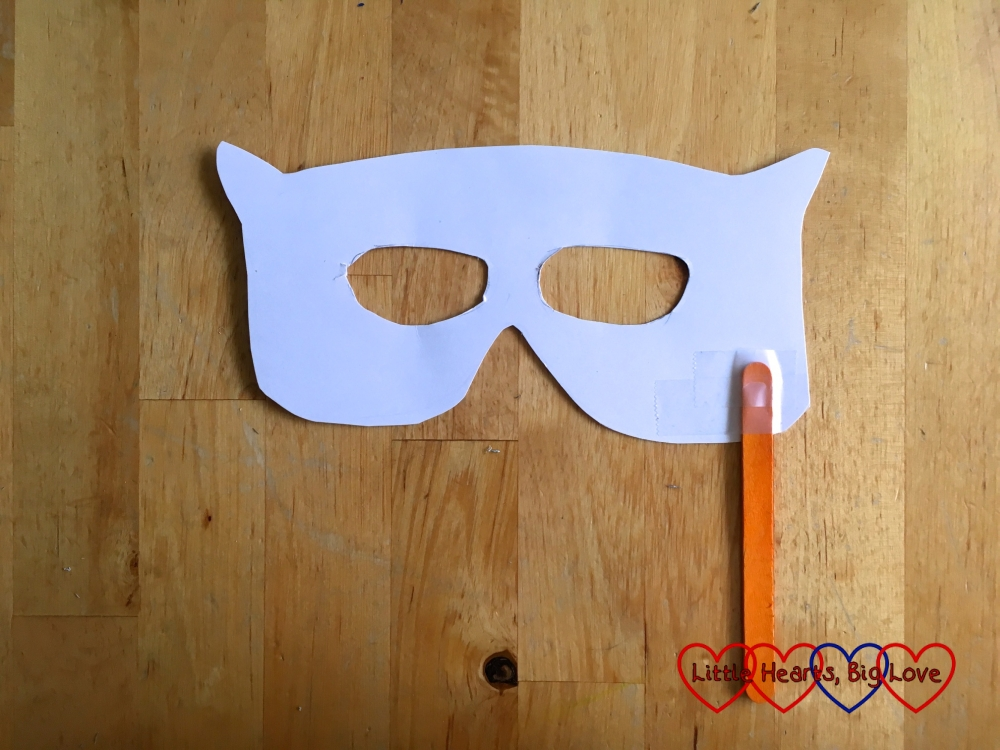 The cardboard mask with a craft stick stuck to one side