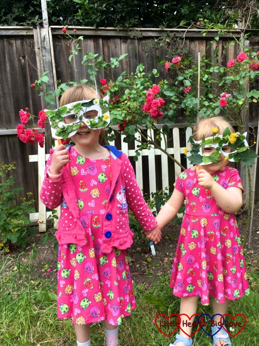Jessica and Sophie standing in the garden with their nature masks