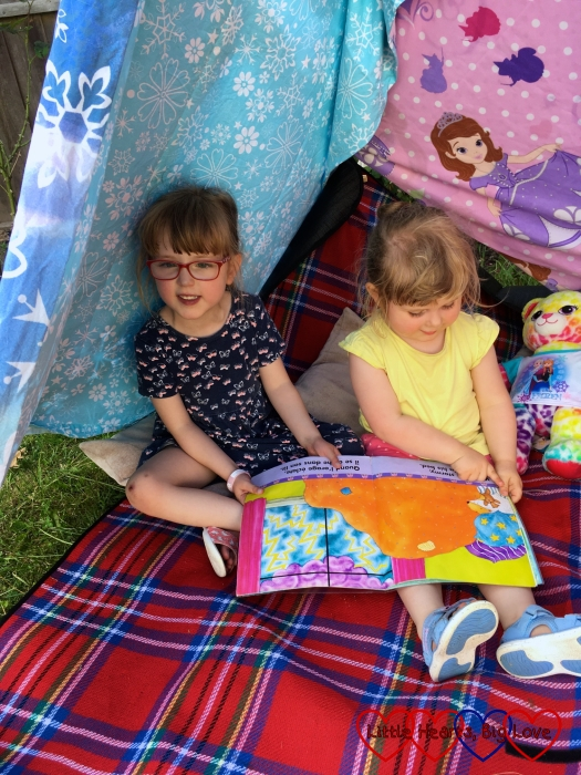 Jessica and Sophie enjoying a story inside the tepee