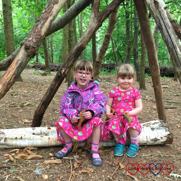 Jessica and Sophie sitting inside a den holding sticks