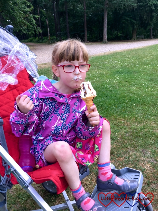 Jessica with an ice-cream moustache, sitting in her buggy and eating an ice-cream
