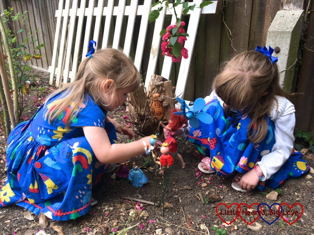 Jessica and Sophie playing with their dolls near the fairy houses