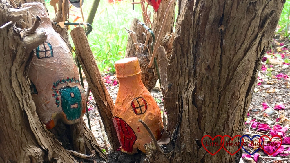 Two painted fairy houses nestled in a buddleia tree stump