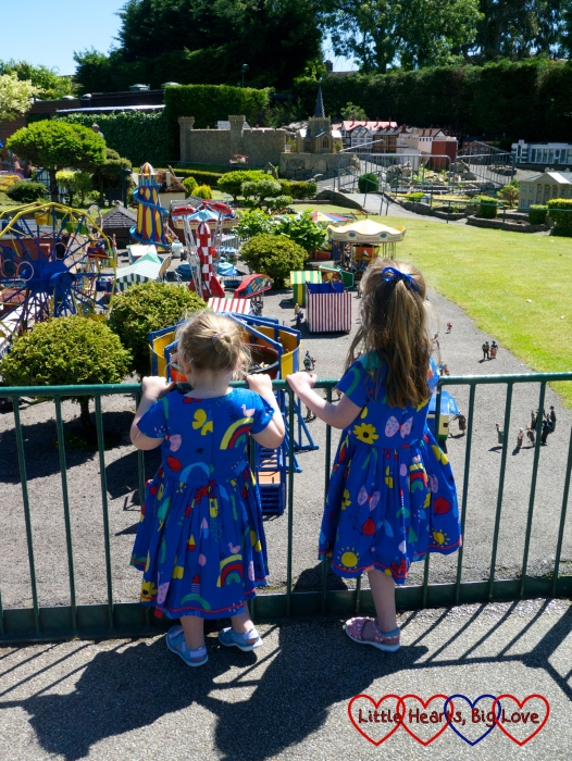 Jessica and Sophie in matching blue dresses looking at the funfair at Bekonscot Model Village