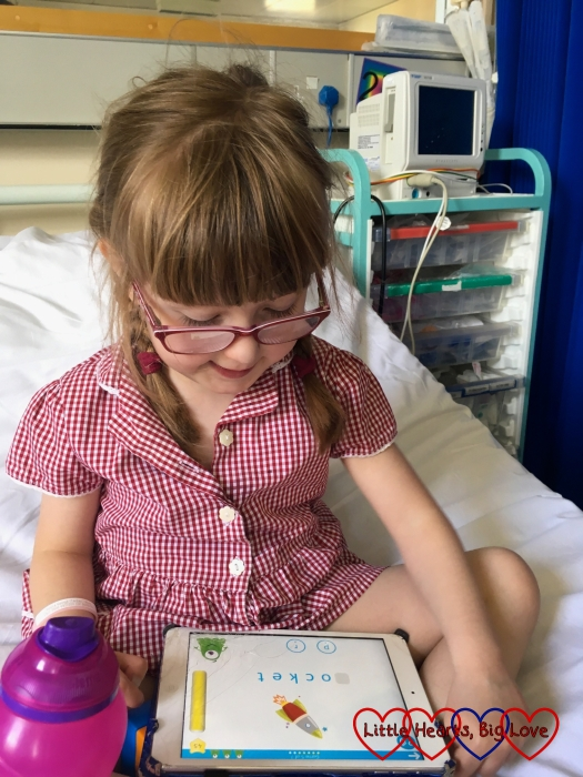 Jessica sitting in the hospital, playing the Read with Fonics game on the iPad