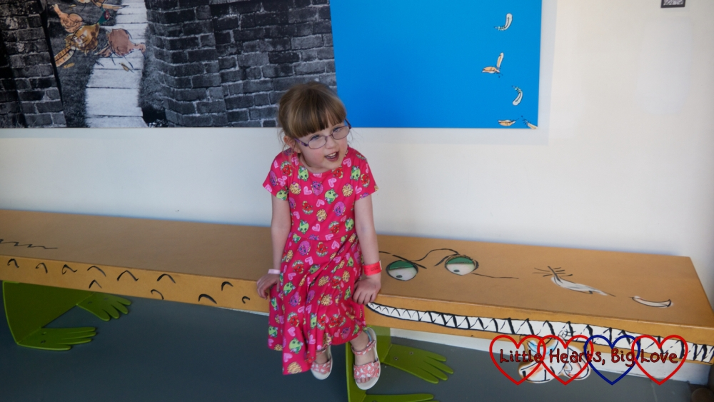 Jessica sitting on the Enormous Crocodile bench