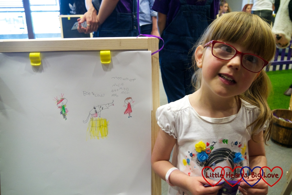 Jessica with her finished picture of Buttons the cow, herself and Kerry the dolly