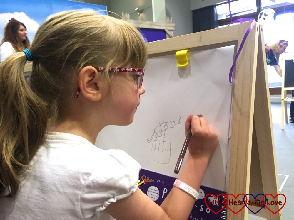 Jessica concentrating on her drawing of Buttons the cow