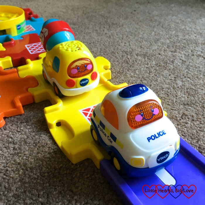 Two VTech cars - a police car and cement mixer on some track