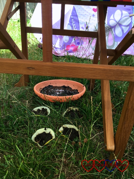 "Sophie's mud cakes ""baking"" under a garden chair"