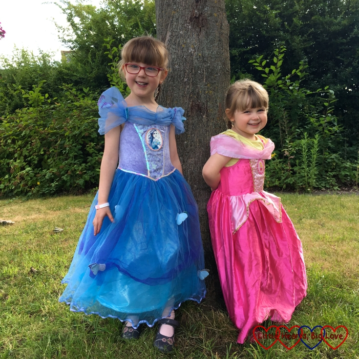 Jessica and Sophie standing by a tree wearing princess dresses