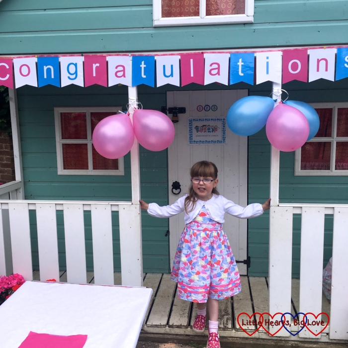 "Jessica standing underneath a ""congratulations"" banner at her preschool leavers party"