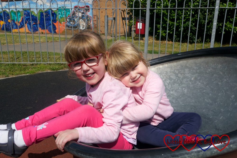 Sophie giving Jessica a hug in the spinner at the park