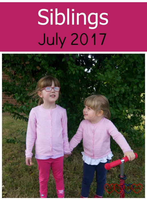 "Jessica and Sophie standing by a tree with Sophie holding Jessica's hand and looking at her - ""Siblings - July 2017"""