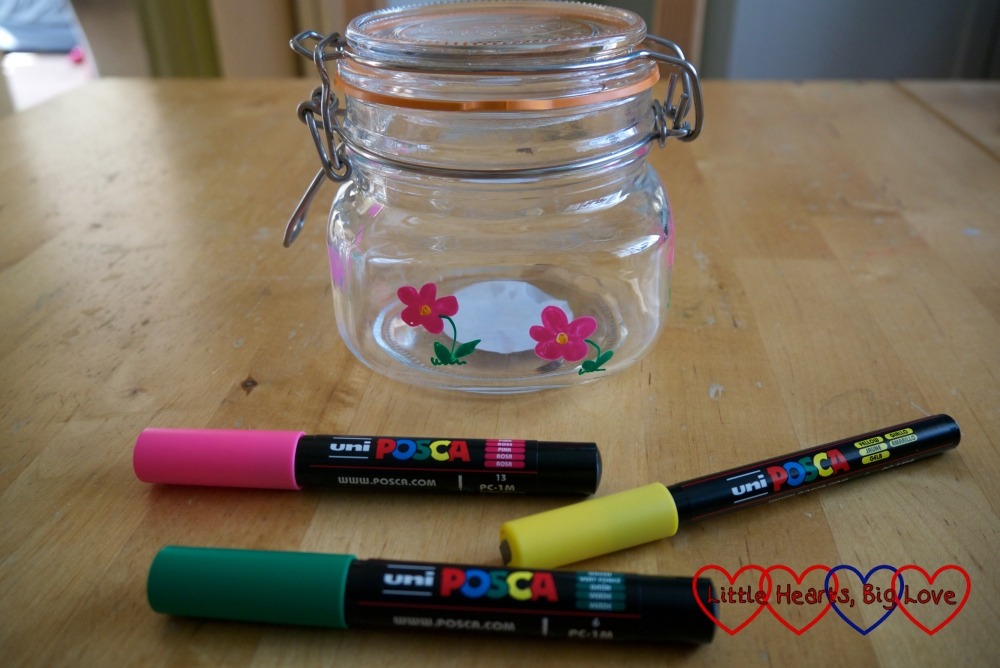 A jar decorated with pink and yellow flowers with POSCA markers in the foreground