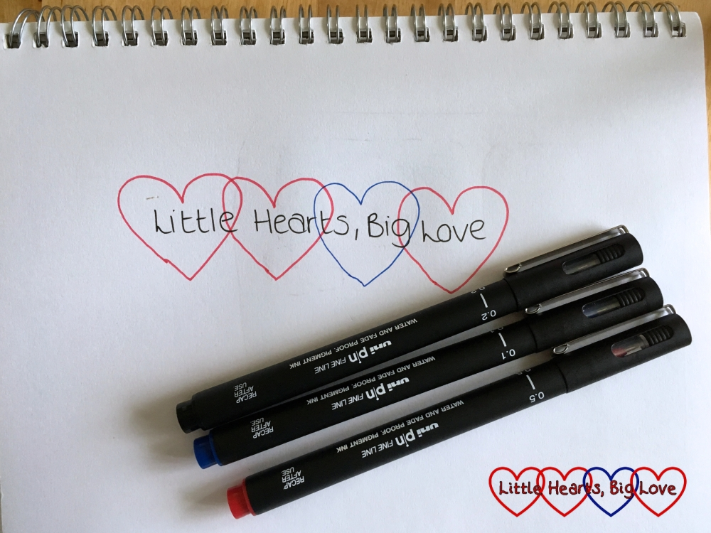 The Little Hearts, Big Love logo (four interlinked hearts - three red, one blue with Little Hearts, Big Love in the middle of the hearts) on a piece of paper with three Uni PIN fine-line drawing pens in red, blue and black