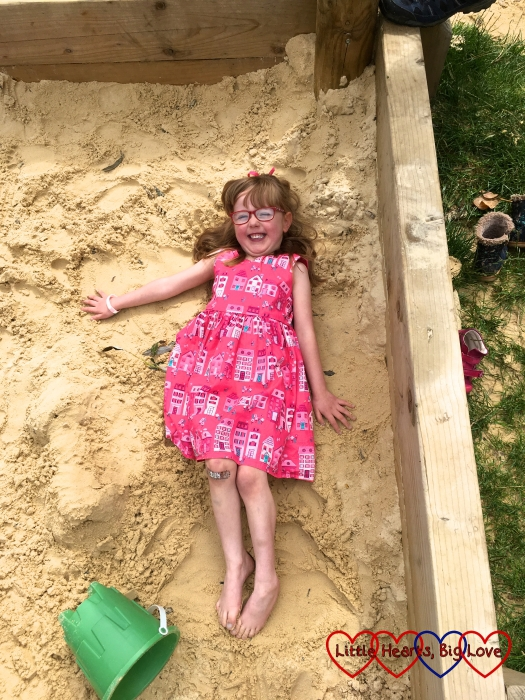 Jessica making a sand angel in the sand pit