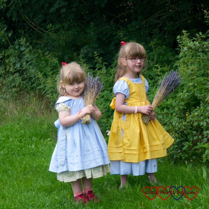 Jessica and Sophie in vintage style dresses and pinafores, holding bunches of lavender