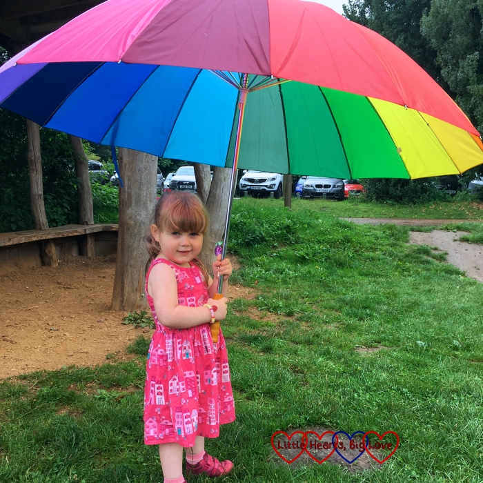 Sophie with a big rainbow coloured umbrella