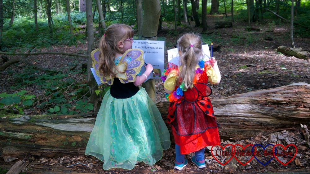 Jessica and Sophie in princess dresses and fairy wings looking at one of thes signs for the fairy trail in Black Park
