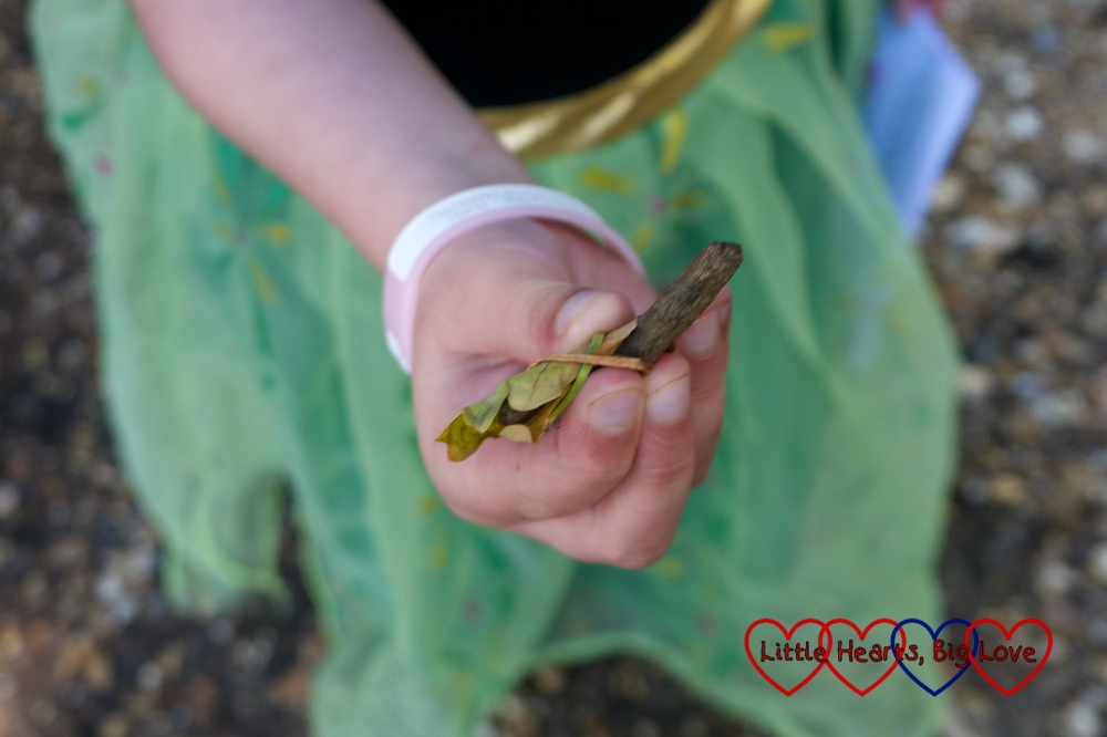 """Jessica holding a tiny stick with a """"fairy shoe"""" made from a leaf with a long blade of grass wrapped around it"""