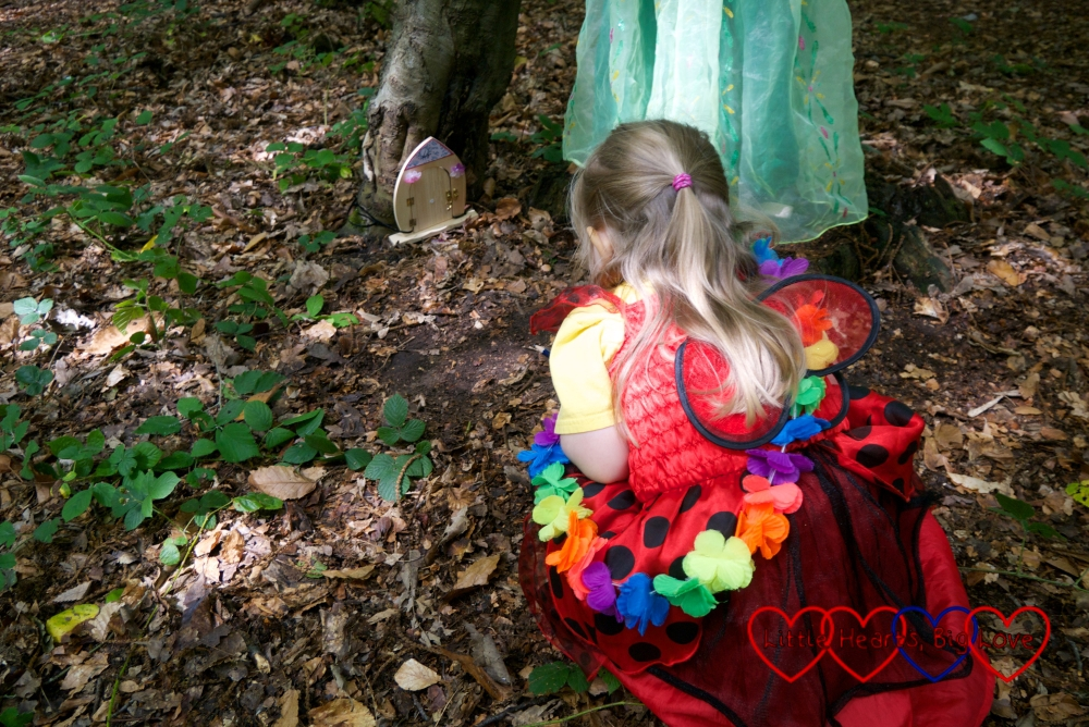 Sophie wearing a ladybird spotted dress with wings looking closely at a fairy door in the woods