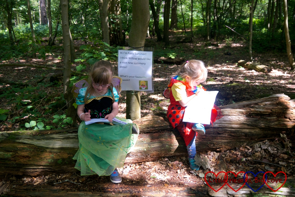 Jessica and Sophie sitting on a log and writing on the activity sheets for the fairy trail