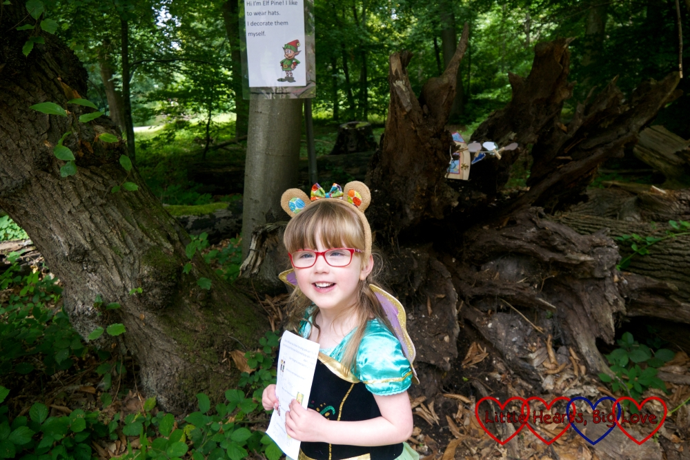 Jessica wearing a princess dress, fairy wings and teddy bear ears standing by one of the fairy trail points in Black Park