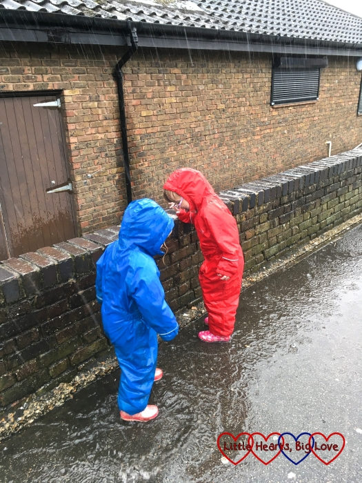 Jessica and Sophie wearing puddlesuits and wellies and splashing in puddles in the rain