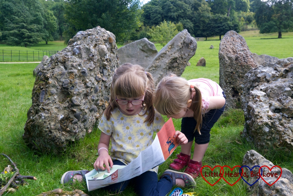 Jessica and Sophie looking at a map together and sitting in amongst the prehistoric stones at Stonor Park