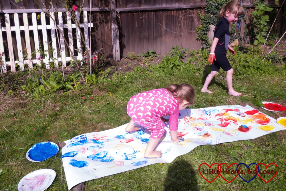 Sophie walking on all fours across a piece of footprint-and-handprint covered lining paper