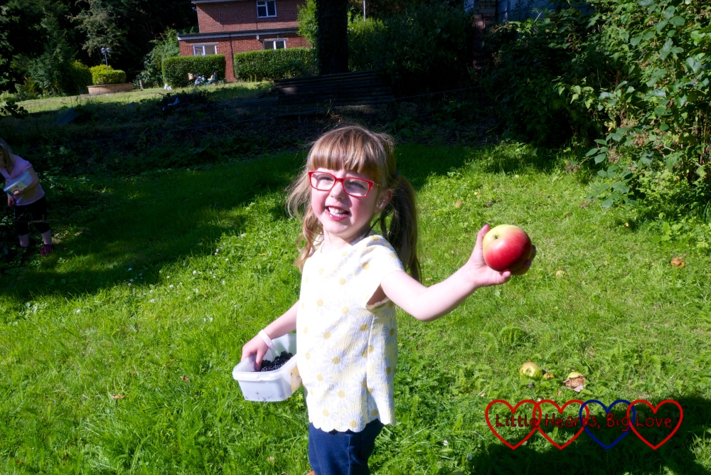 Jessica with a tub of freshly picked blackberries, holding out a freshly picked apple in Grandma's garden