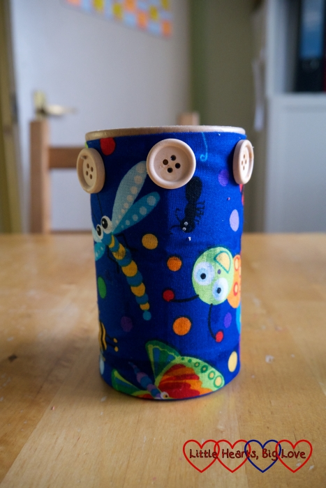 A pencil pot made from a cardboard pot wrapped in fabric with buttons stuck to it