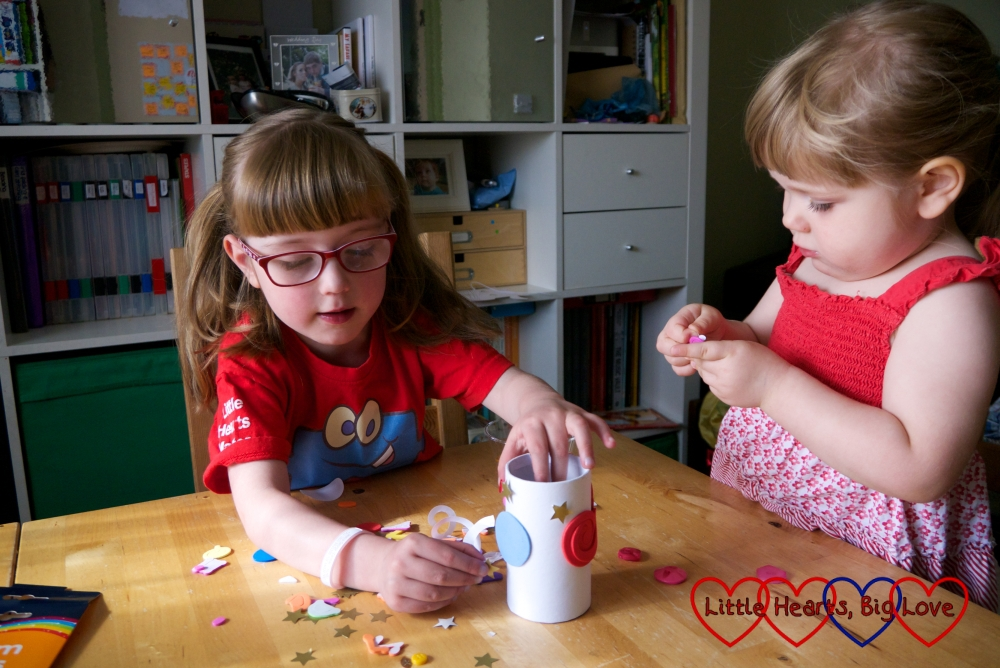 Jessica and Sophie sticking foam shapes to a cardboard pot