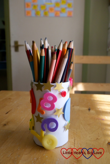 A pencil pot decorated with foam shapes and stars and filled with coloured pencils