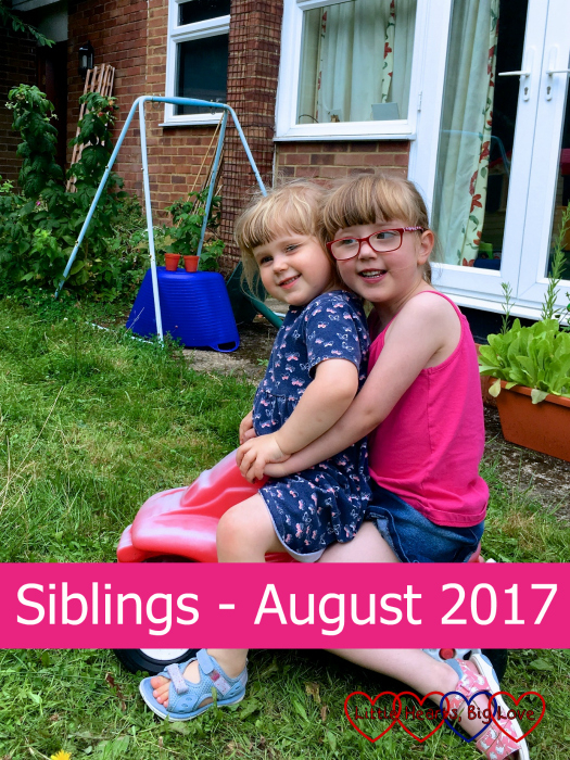 """Jessica and Sophie sitting on a ride-on bike together - """"Siblings - August 2017"""""""