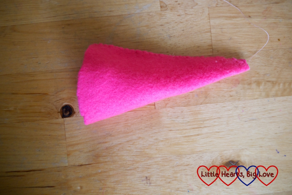 A cone of pink felt folded and stitched down the long side.