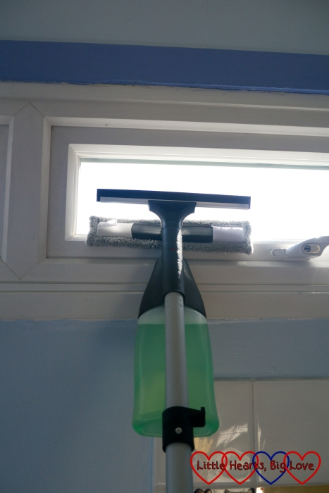 Cleaning a small window with the window cleaning attachment on the spray mop