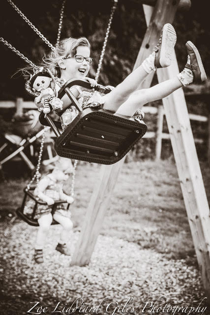 A black and white shot of Jessica on a swing