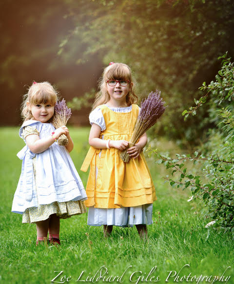 Jessica and Sophie wearing vintage-style dresses with pinafores and holding bunches of lavender