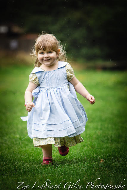 Sophie wearing a vintage-style dress and pinafore running towards the camera
