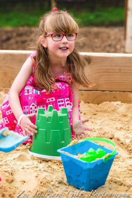 Jessica in a pink dress playing in a sandpit