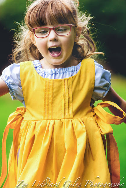 Jessica wearing a vintage-style dress and pinafore, running towards the camera with a big smile on her face