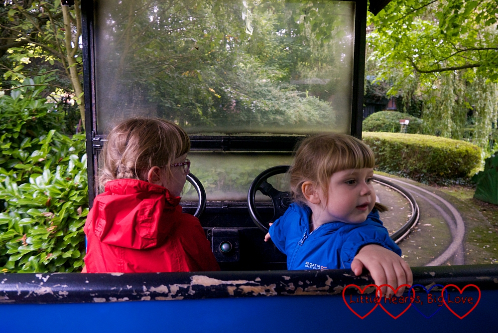 Jessica and Sophie driving a car on the Toadie's Crazy Cars ride at Chessington World of Adventures
