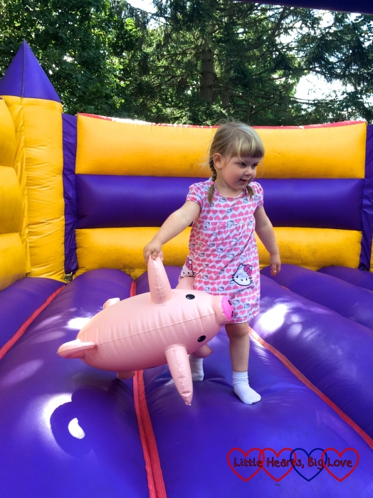 Sophie bouncing on a bouncy castle with an inflatable pig